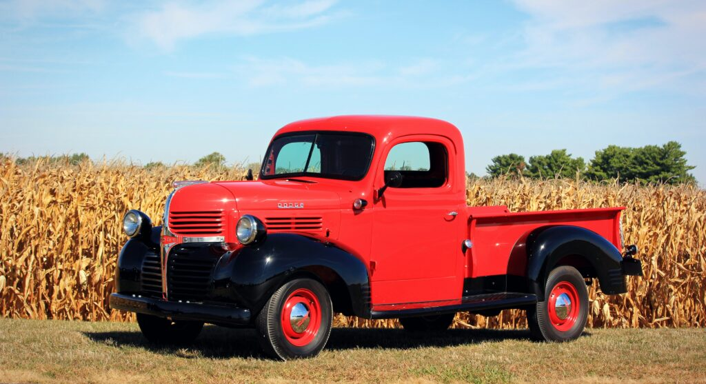 A cherry red, old-fashioned pickup truck beside a cornfield during a romantic getaway in Ohio.