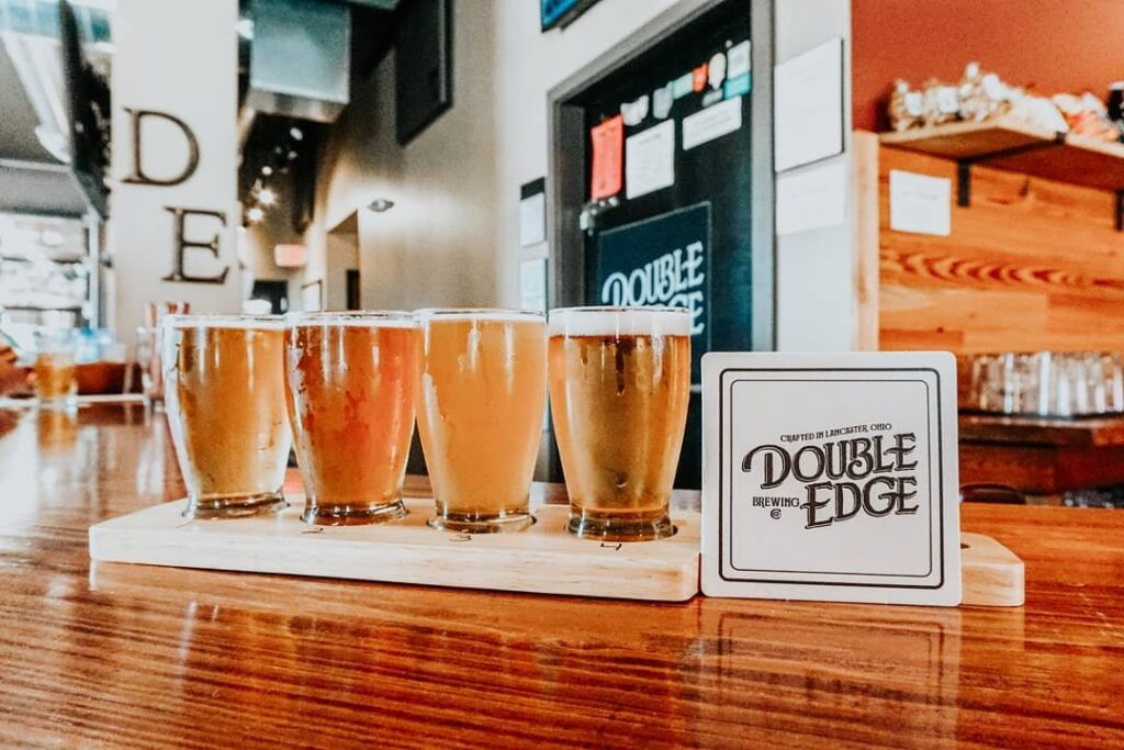 Four drinks on the bar top inside Double Edge Brewing Company.