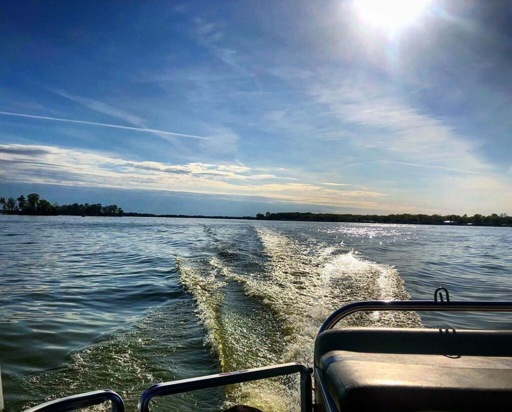 The wake off the back of a fishing boat on a lake with a distant tree shoreline.