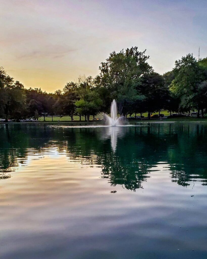 A fountain in the middle of a pond at Rising Park.