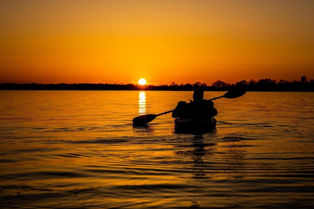 The silhouette of a person in a canoe paddling out under an orange sky.