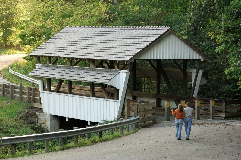 Two people pointing at a covered bridge; enjoying one of Fairfield County's most popular things to do this summer.