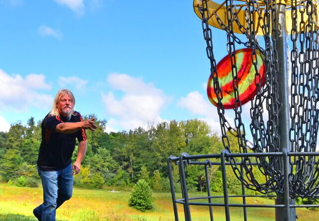 For a summer activity, a man with long, blonde hair tossing a red and yellow disc golf disc into the chain trap.
