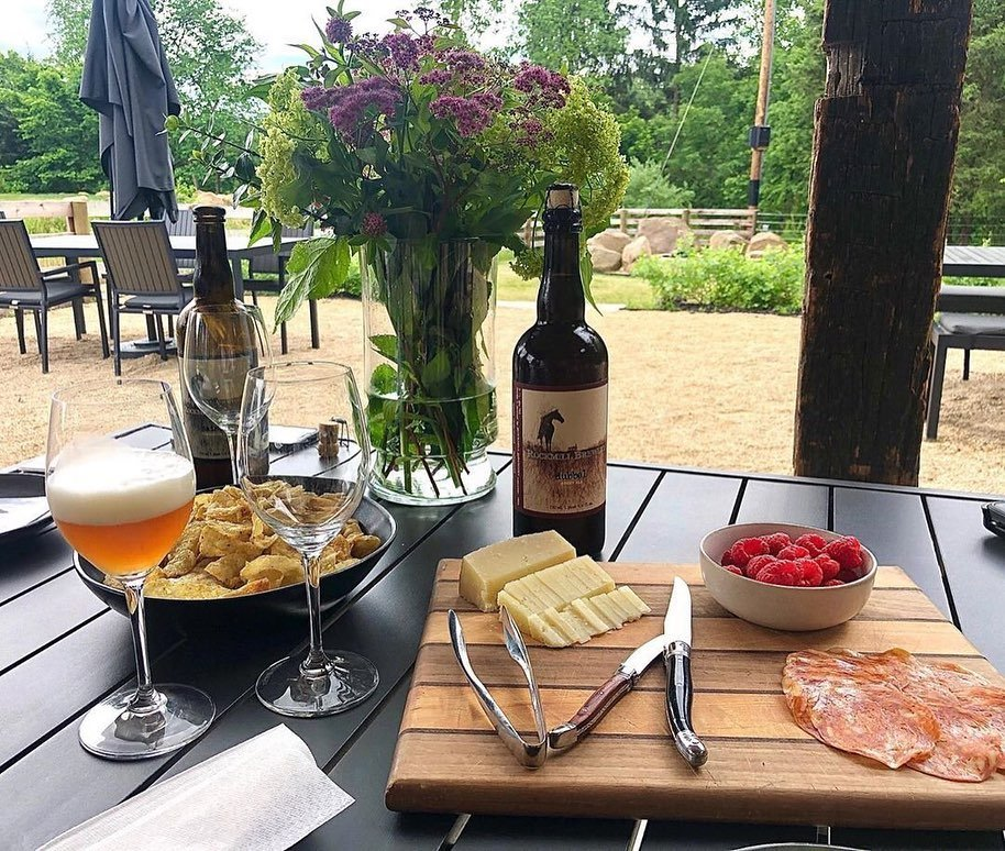 A spread of Rockmill Brewery wine, fine cheeses, fruit, and more on a patio table with flowers.