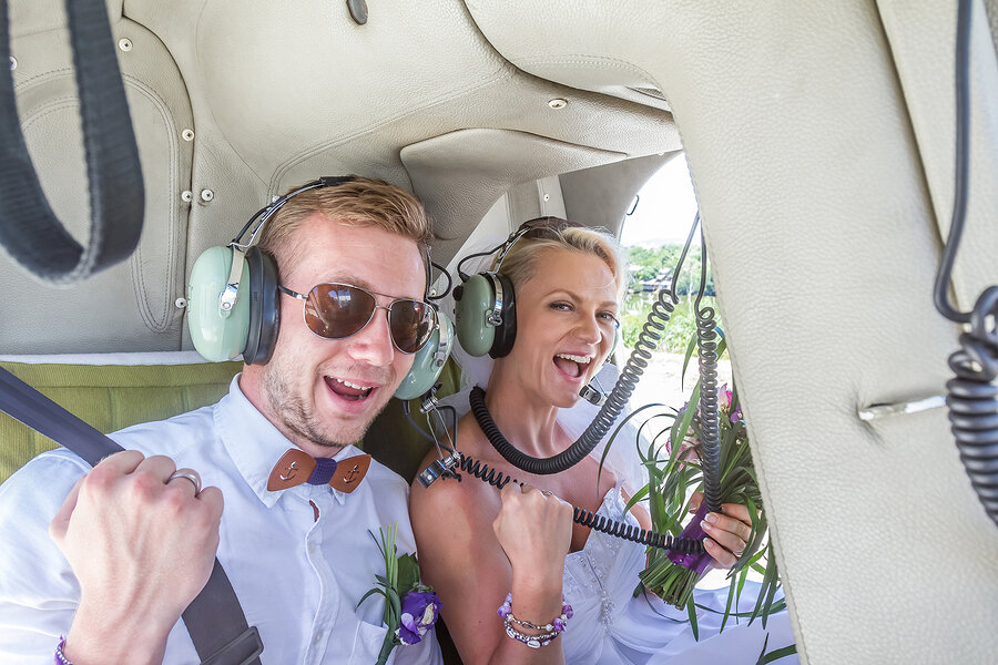 A man and woman smiling with headsets on during a helicopter tour.