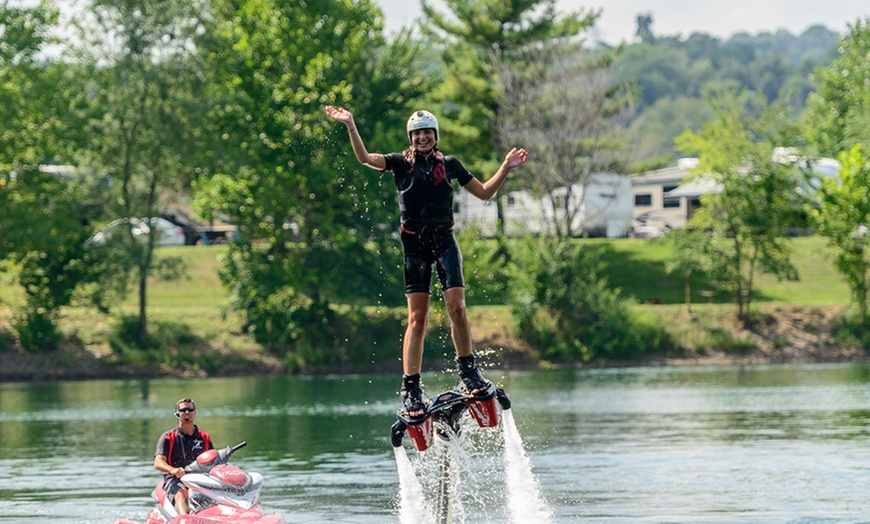 A woman waving her right hand on a water-powered jet pack hovering above a lake.