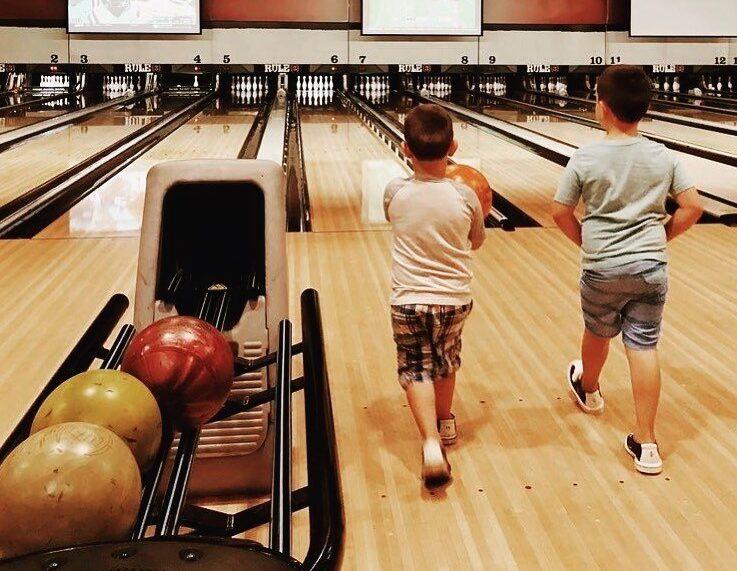 Two boys walk up a bowling lane to bowl.