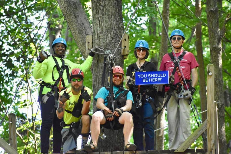 """A group of people in ziplining gear with a sign that says, """"You should be here."""""""