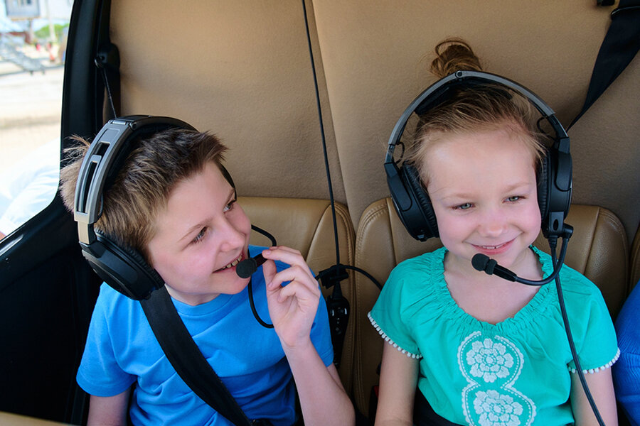 A young boy and a young girl smiling with headsets on during a helicopter ride.