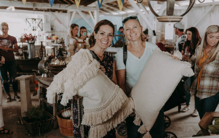 Two women holding decorative pillows and smiling at a marketplace.