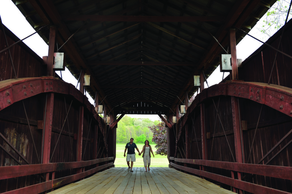 A couple holds hands on a covered bridge.
