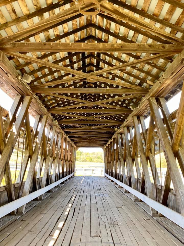 View of the inside ceiling of a covered bridge with intricate woodwork.