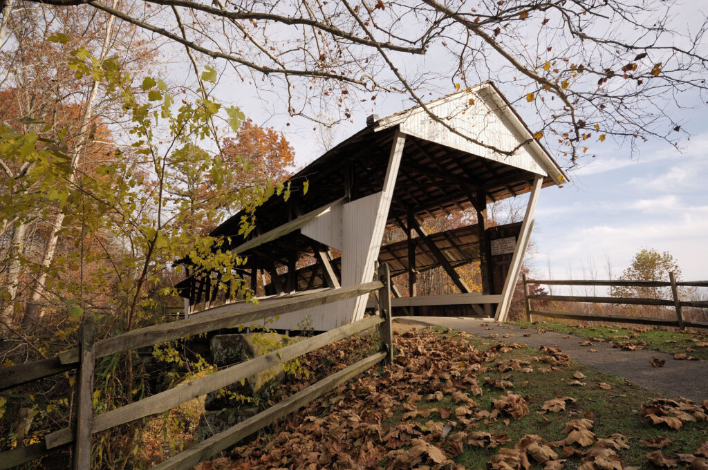 A covered bridge by burnt orange leaves on the ground.