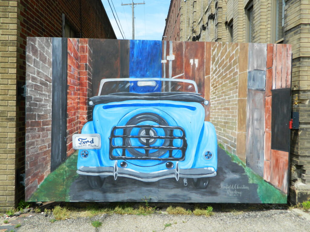 Mural of a blue car in an alley.