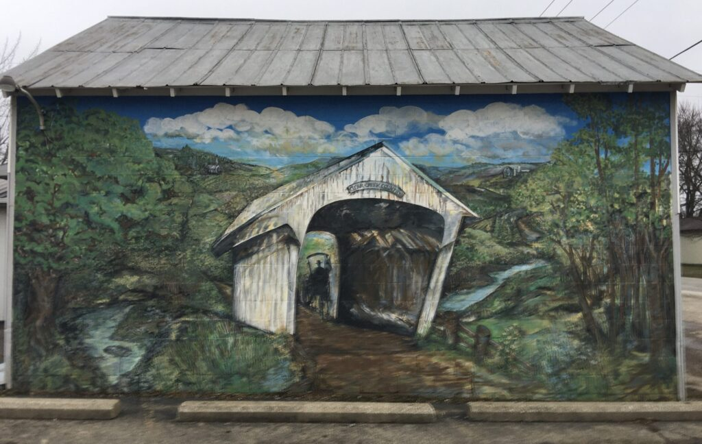 A painting of a covered bridge on the side of a building.