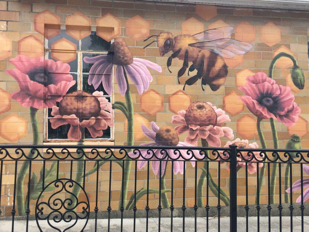 Mural art depicting a honeybee and flowers.