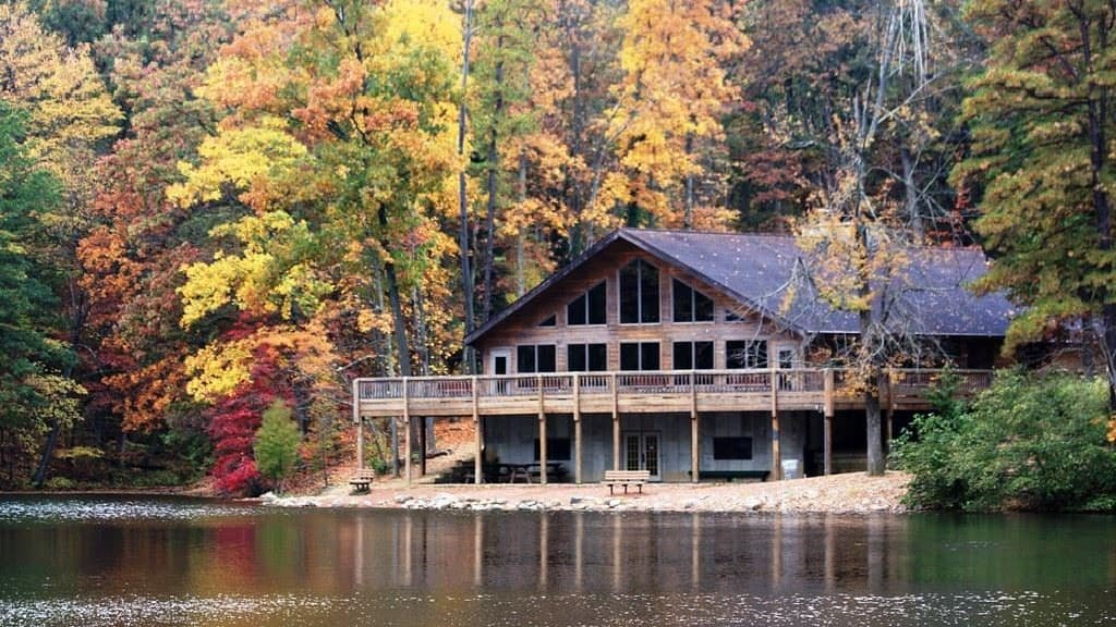 A lodge on the water at Alley Park with a forest of Ohio fall foliage behind it.