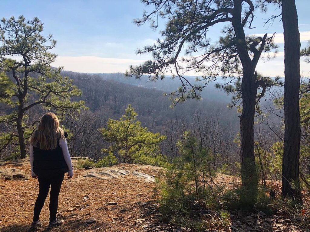 A woman in a long-sleeve shirt and vest standing at the Christmas Rocks overlook after a fun hike.