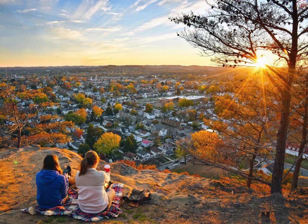 Two women enjoying the view from a checkered picnic blanket on Mount Pleasant overlooking a town.