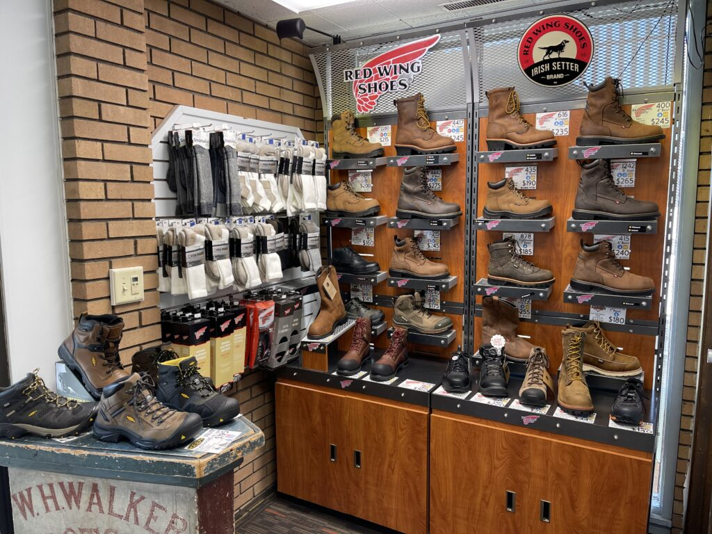 A boot retail display beside a rack with pairs of sock for sale at Walker's Shoe Center.
